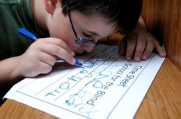 Boy wearing glasses writes on his time sheet with a thick blue marker.